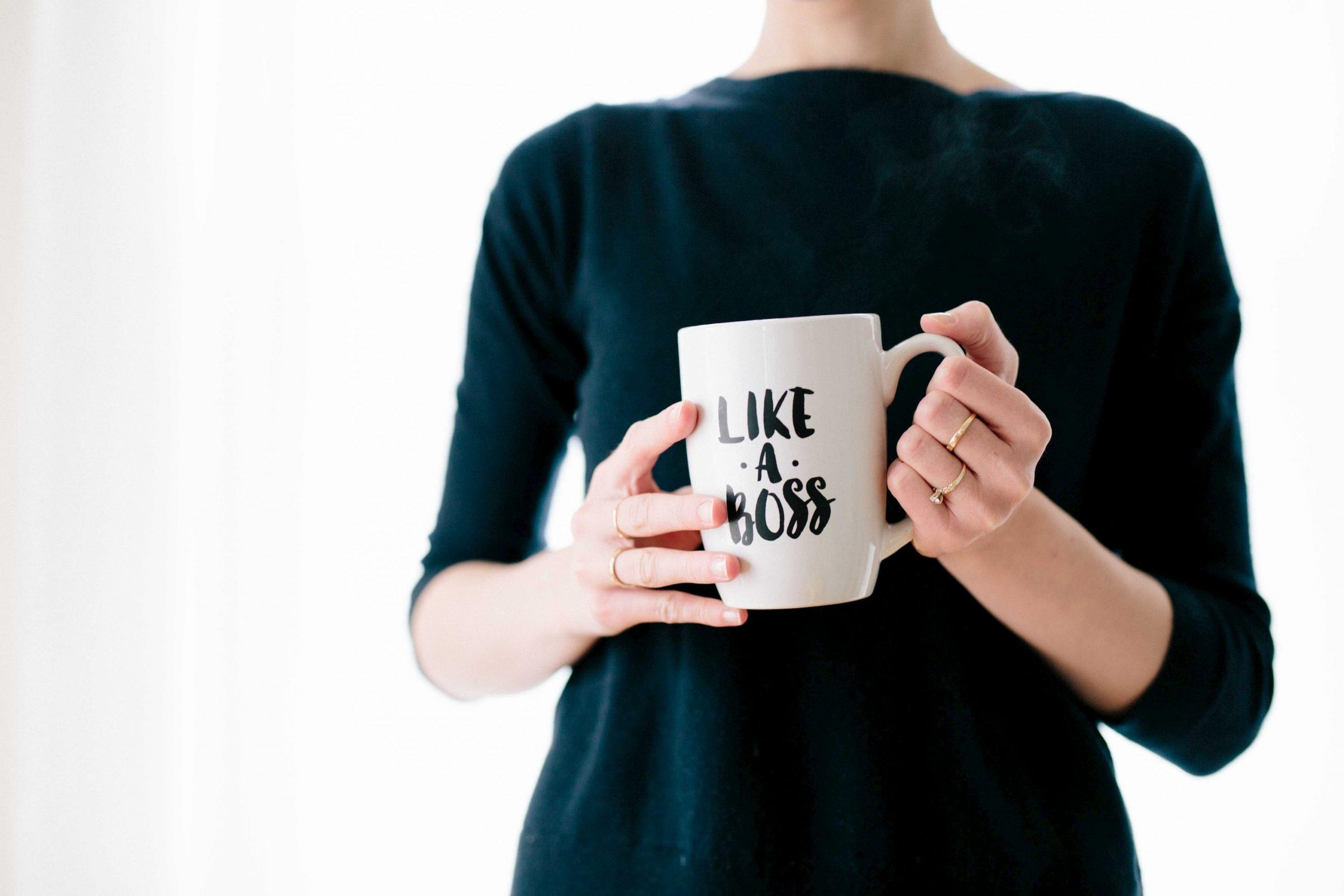 Woman manager holding boss-themed mug